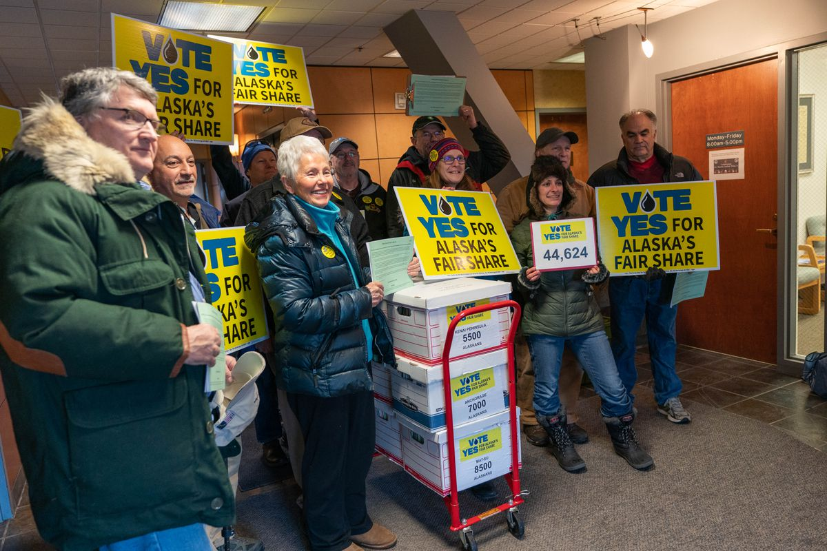 Supporters of the group Vote Yes for Alaska's Fair Share prepare to turn in signature booklets on Jan. 17, 2020 at the Alaska Division of Elections in Anchorage. The ballot measure the group supports would apply to the North Slope's large legacy fields and would bring in about $1 billion extra in production taxes annually, according to the group's chairman, Robin Brena. (Loren Holmes / ADN archive)