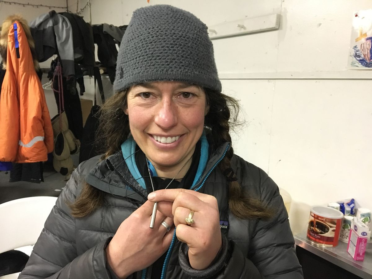 Iditarod musher Kristin Bacon wears a necklace charm that carries ashes of long-time Iditarod volunteer Cyndy Fritts. (Tegan Hanlon / Alaska Dispatch News)
