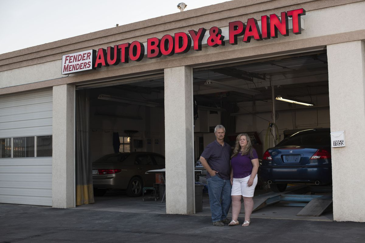 Scott and Tammy Nelson, co-owners of Fender Menders, an auto body shop, pose in front of their garage in Broomfield, Colo. The Nelsons accepted a PPP loan in April, which ran out at the end of June. (Photo by Rachel Woolf for The Washington Post)
