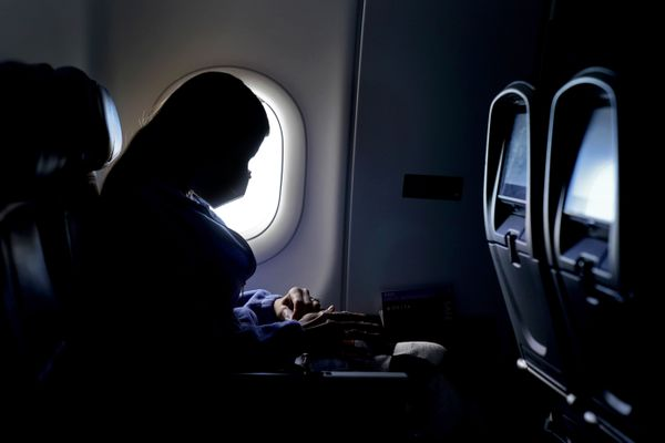 FILE - In this Wednesday, Feb. 3, 2021 file photo, a passenger wears a face mask during an airline flight after taking off from Atlanta. On Friday, April 2, 20201, the Centers for Disease Control and Prevention updated its guidance to say fully vaccinated people can travel within the U.S. without getting tested for the coronavirus or going into quarantine afterward. (AP Photo/Charlie Riedel)