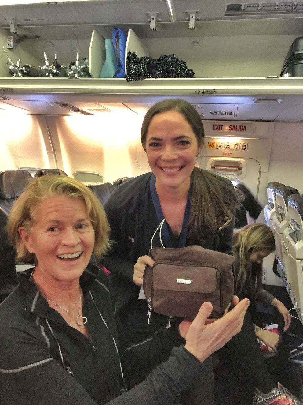 Leah, seated, left her purse in the airport. One of the Alaska Airlines lounge hosts ran to the plane and handed it to flight attendant Robyn to return to Leah. (Photo: Scott McMurren)