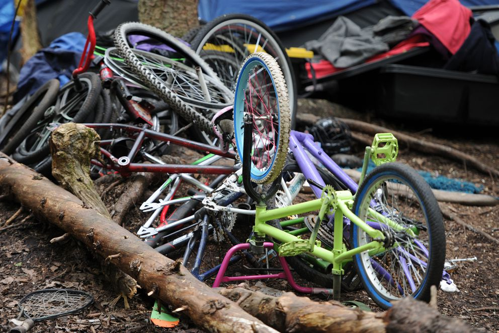 Bicycles frames and tires stacked at a homeless camp along the Chester Creek Trail in Anchorage on Tuesday, May 15, 2018. (Bill Roth / ADN)