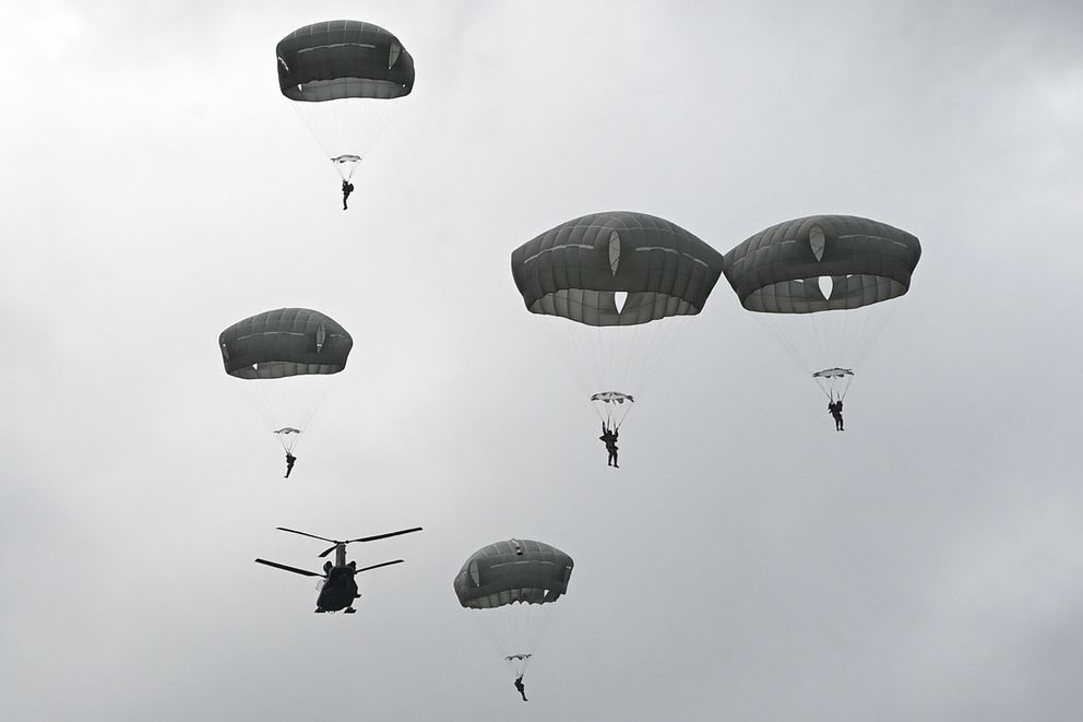 Paratroopers float to the ground after jumping from a CH-47 Chinook helicopter on Tuesday. (Bill Roth / ADN)