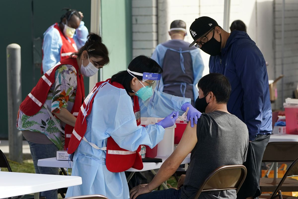 FILE - In this Jan. 13, 2021, file photo, health care workers receive a COVID-19 vaccination at Ritchie Valens Recreation Center, Wednesday, Jan. 13, 2021, in Pacoima, Calif. (AP Photo/Marcio Jose Sanchez, File)