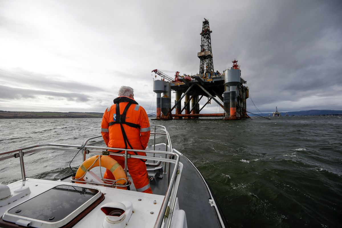 An employee stands on the deck of a pilot boat in view of the Ocean Princess oil platform, operated by Diamond Offshore Drilling Inc., in the Port of Cromarty Firth in Cromarty, Scotland, on Feb. 16, 2016. (Matthew Lloyd / Bloomberg)