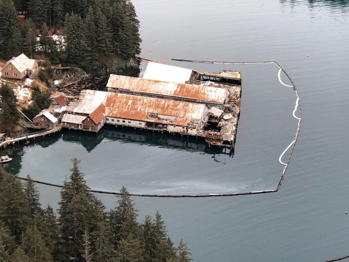 Containment boom around the collapsed dock structure at Port William in Shuyak Strait, Kodiak Island. (Photo Courtesy of Alaska Chadux Corporation via U.S. Coast Guard)