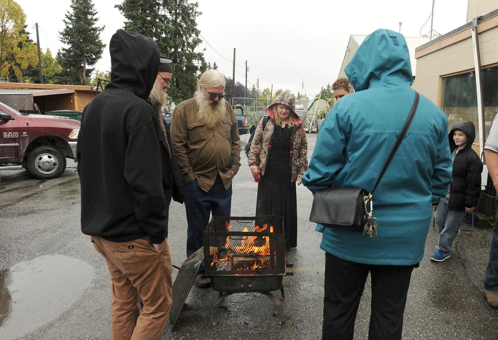 Rich McCreadie (father of Daniel McCreadie), third from the left, and others stand around a fire pit during a memorial for the men killed in a shooting at The Bullion Brothers store last week. (Bob Hallinen / Alaska Dispatch News)