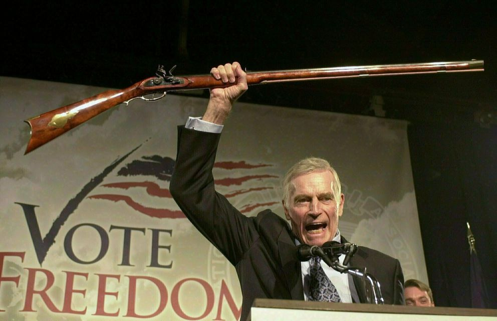 FILE - In this Oct. 21, 2002 file photo, National Rifle Association President Charlton Heston holds up a rifle as he addresses gun owners during a 'get-out-the-vote ' rally in Manchester, N.H. While American gun-rights are enshrined in the U.S. Constitution - something that doesn't translate to most countries around the world - the NRA's track record of aggressively shaping the debate has nevertheless turned it into the go-to group for other gun-rights activists outside the U.S. (AP Photo/Jim Cole, File)