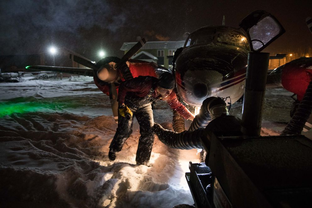 Matt Gallagher, a pilot for Warbelow's Air, cleans snow off the airplane in subzero temperatures before taking off for a flight to Beaver at the airport in Fairbanks on Dec. 2. (Ruth Fremson/The New York Times)
