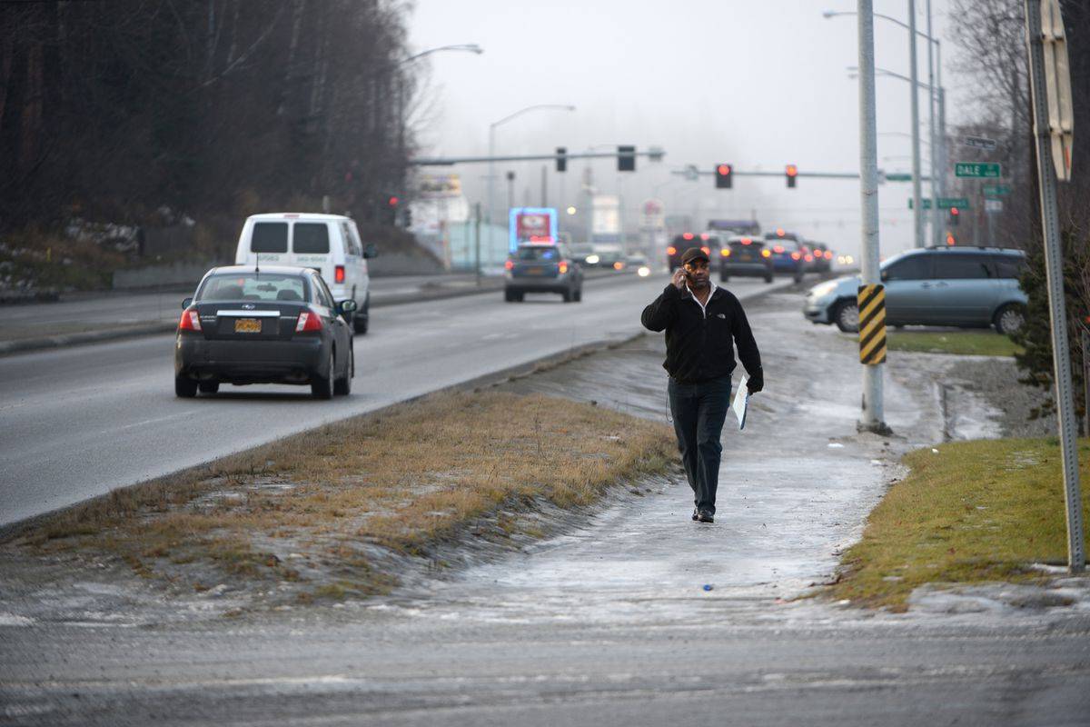 Renardo Felipe Fox negotiates a very icy sidewalk next to Tudor Road, Nov. 21, 2018 on his way to the busstop. Fox had just finished a job interview and was making his way home to start preparing for Thanksgiving. Many sidewalks, roads, parking lots and trails are solid ice. (Anne Raup / ADN)