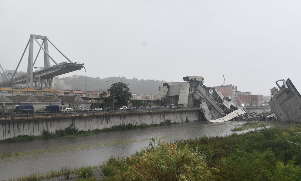 A view of the collapsed Morandi highway bridge in Genoa, northern Italy, Tuesday, Aug. 14, 2018. A large section of the bridge collapsed over an industrial area in the Italian city of Genova during a sudden and violent storm, leaving vehicles crushed in rubble below. (Luca Zennaro/ANSA via AP)