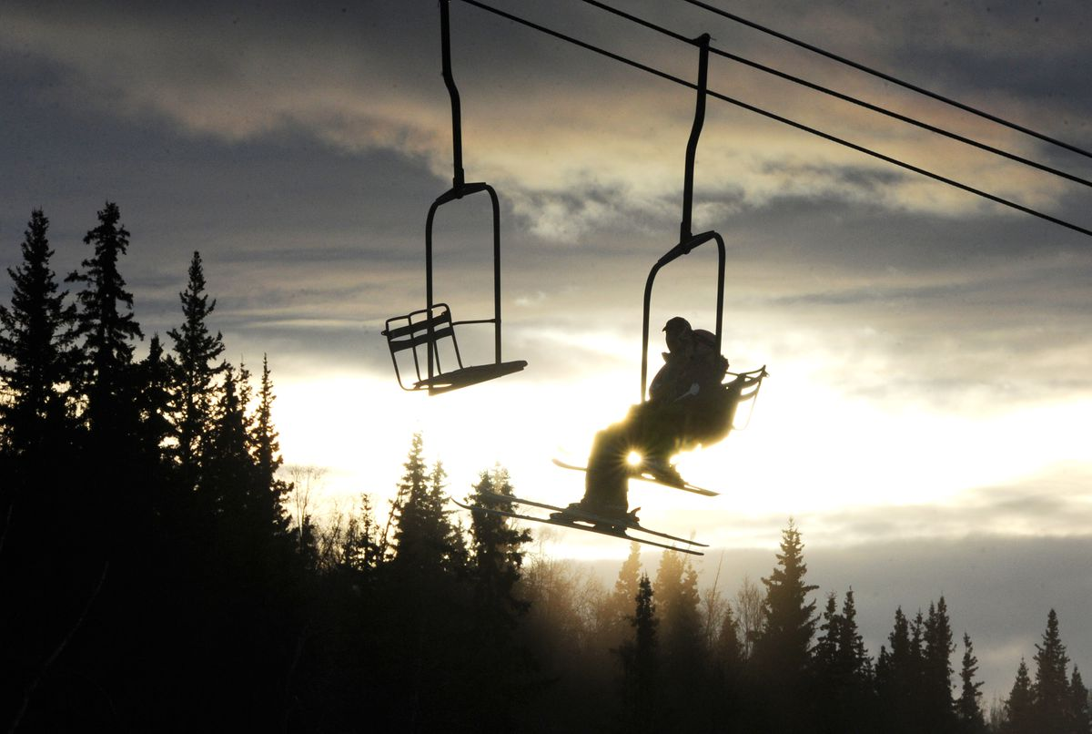 Skiers ride the chair lift at Hilltop Ski Area as the clouds move in. Hilltop plans to close for the season on April 2. (Bill Roth / Alaska Dispatch News)