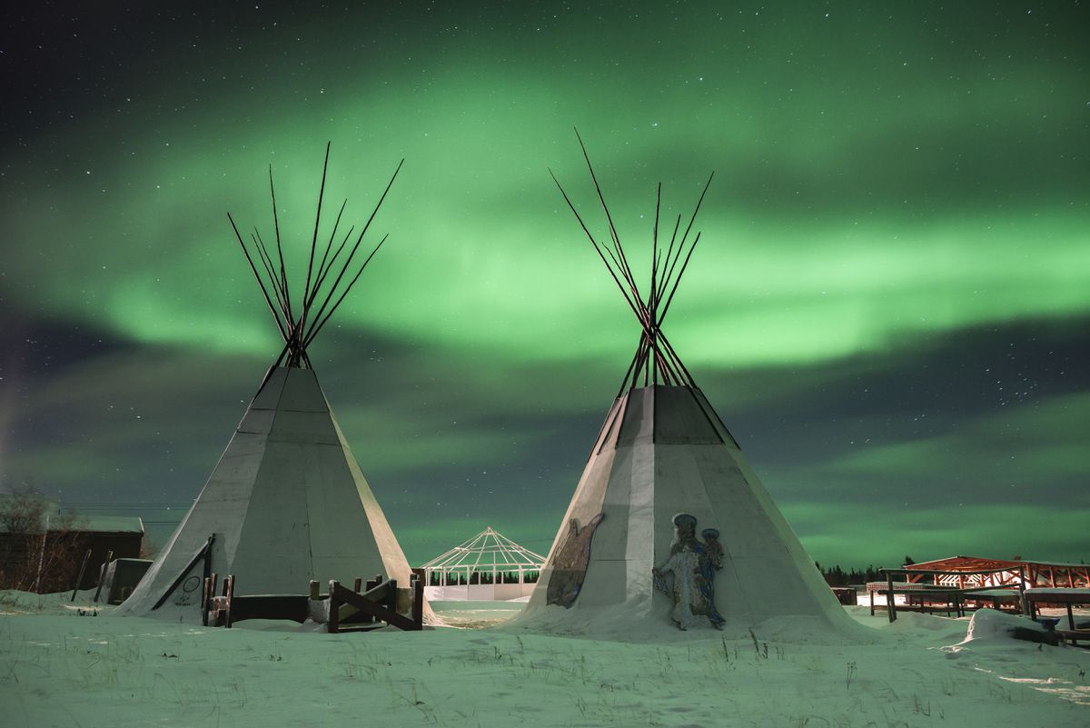 The northern lights illuminate lodges used for smoking fish and drying meat in Deline, a village on Great Bear Lake in Canada's Northwest Territories, Dec. 1, 2016. Alone among the world's 10 biggest lakes, Great Bear is unspoiled, and the Sahtuto'ine people who live here are fiercely dedicated to protecting it and were recently granted self-government by Canada. (Christopher Miller / The New York Times)
