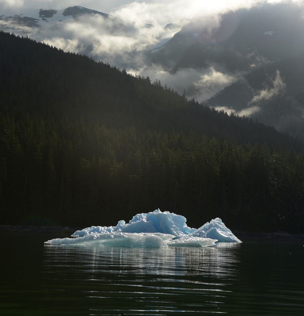 An iceberg floats on the waters of Holkham Bay as clouds form in the valleys of the Tongass National Forest. (Bob Hallinen / ADN)