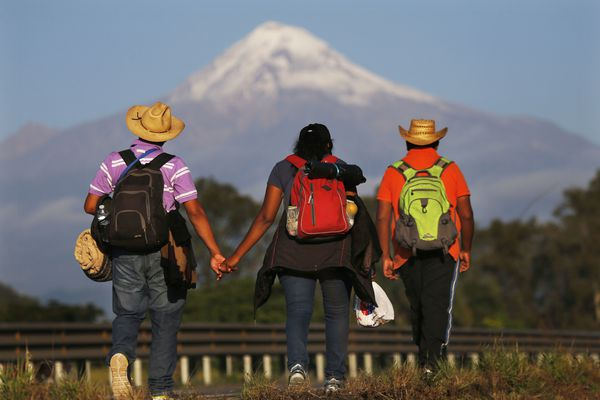 Central American migrants begin their morning trek facing Pico de Orizaba volcano as part of a thousands-strong caravan hoping to reach the U.S. border, upon departure from Cordoba, Veracruz state, Mexico, Monday, Nov. 5, 2018. A big group of Central Americans pushed on toward Mexico City from a coastal state Monday, planning to exit a part of the country that has long been treacherous for migrants seeking to get to the United States. (AP Photo/Marco Ugarte)