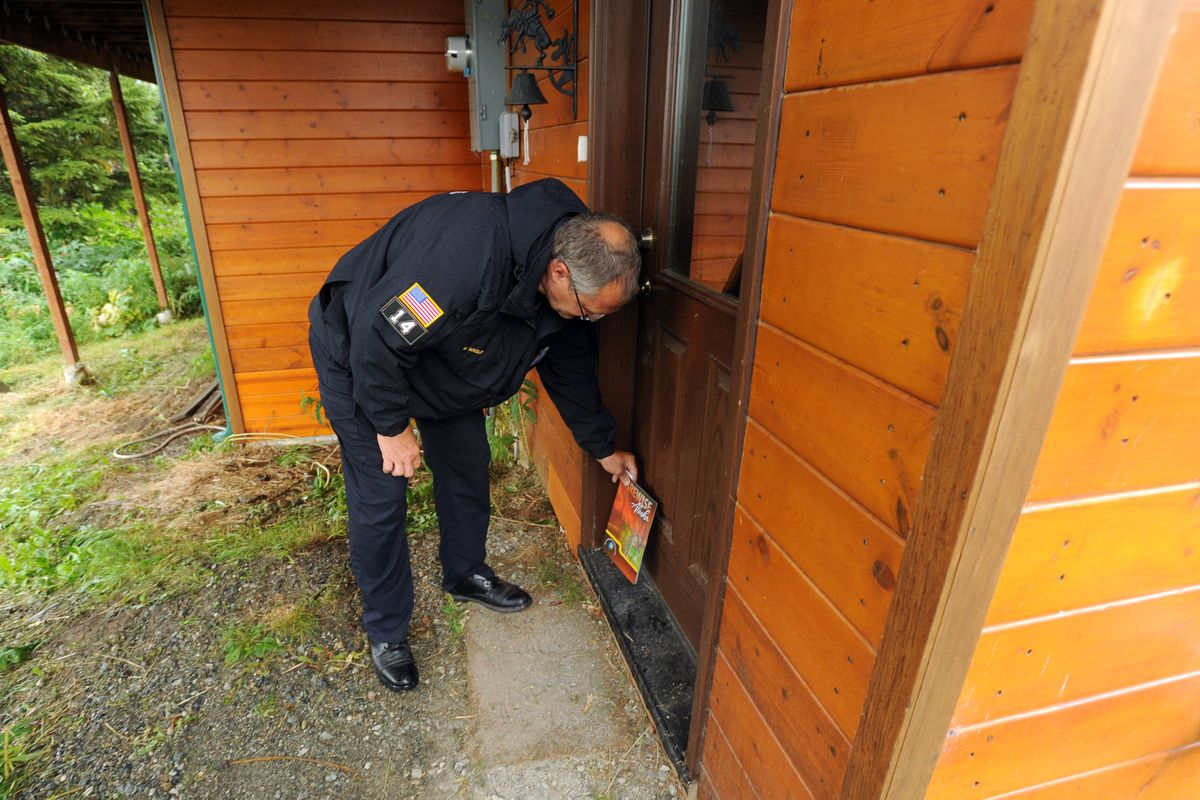 Anchorage Fire Department Capt. Marc Nokelby leaves a booklet during a Firewise Home Assessment Program visit to properties along Potter Heights Drive prompted by the McHugh Creek wildfire on Friday, July 22, 2016, in south Anchorage. (Erik Hill / Alaska Dispatch News)