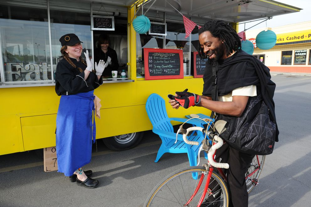 Cyclist Dexter Sims chats with chef and owner Amanda Cash after eating at The Magpie food truck May 20, 2015. (Erik Hill / Alaska Dispatch News)