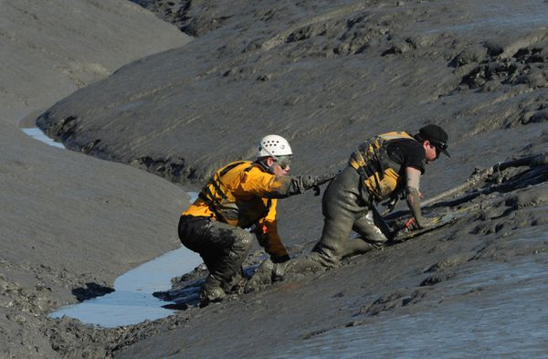 Fisherman Matthew Norbert, right, received help from the Anchorage Fire Department after he got stuck up to his waist while fishing for Silver (Coho) salmon near the mouth of Ship Creek on Tuesday, August 28, 2018. (Bill Roth / ADN)