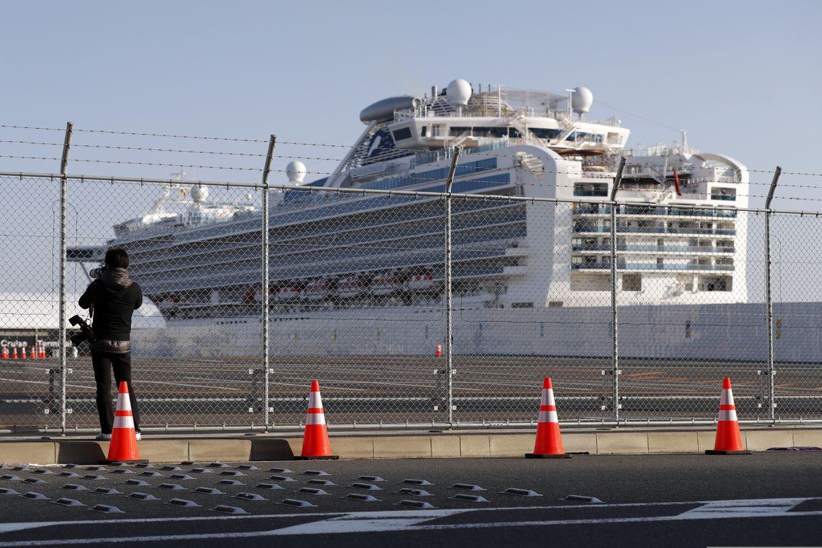 A photographer takes photos near the quarantined Diamond Princess cruise ship anchored at a port in Yokohama, near Tokyo, Friday, Feb. 21, 2020. (AP Photo/Eugene Hoshiko)