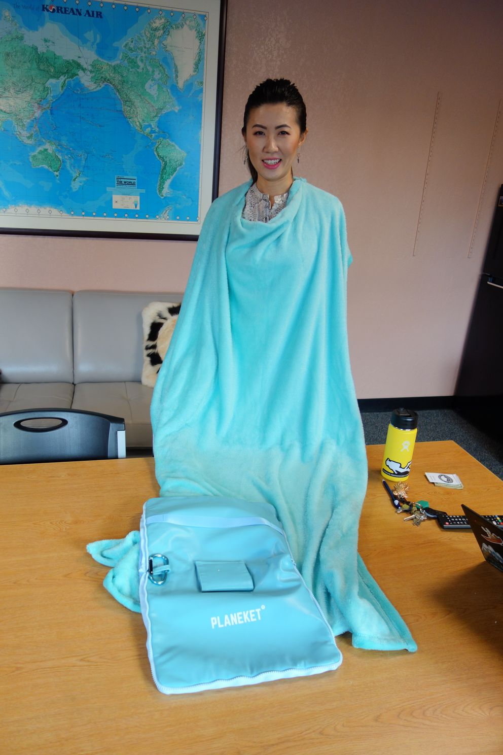Jin Chen shows off the fluffy blanket in the Planeket, which fastens at the top. (Photo by Scott McMurren)