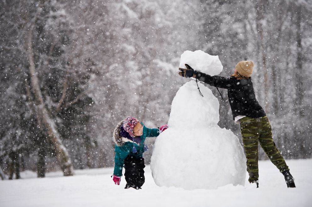 Taylor Quattlebaum, right, adds the head to a snowman at Valley of the Moon Park during a steady snowfall on February 18, 2020. Nine-year-old Olive Brookwell helps at left. (Marc Lester / ADN)