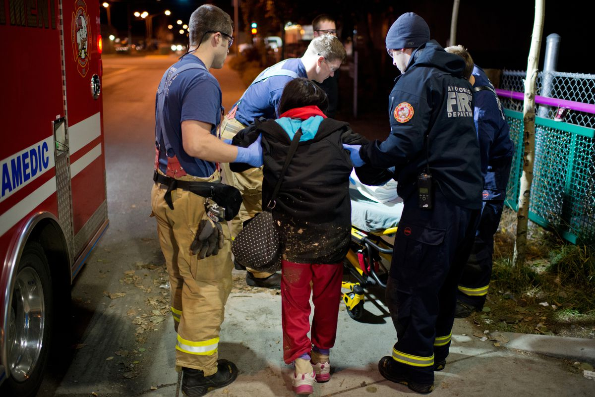 """Anchorage Firefighters assist a woman near 13 Avenue and Hyder Street. The intoxicated woman complained of heart rhythm irregularities and was transported to a hospital. Medic Matt Eckart said the demands on the fire department by intoxicated people can wear down firefighters. """"We take them to the hospital, they release them, they go to Anchorage Safety Patrol and they just sober up to get out and go do this - drinking - again. It's just a big cycle,"""