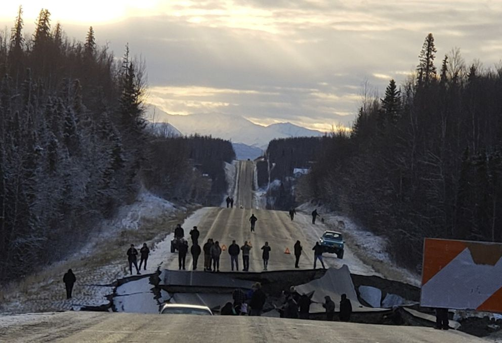 FILE - In this Nov. 30, 2018 file photo, provided by Jonathan M. Lettow, people walk along Vine Road after an earthquake in Wasilla, Alaska. Alaska State Troopers are asking that people do not take selfies in front of the buckled roadway north of Anchorage, Alaska. (Jonathan M. Lettow via AP, File)