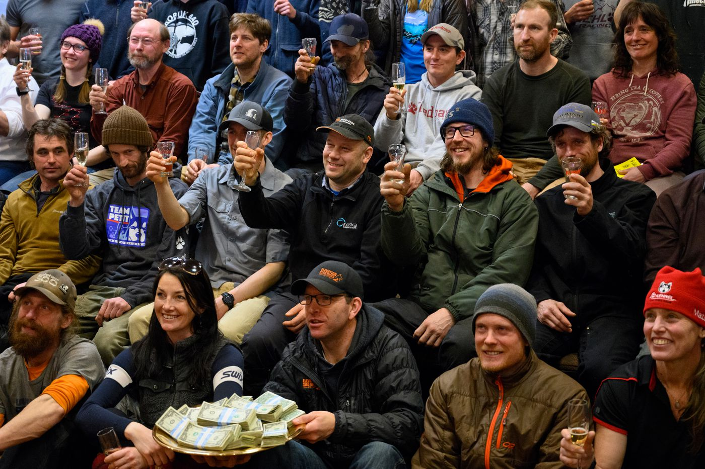 Iditarod mushers gather for a toast at the Lakefront Anchorage hotel on March 5, 2020. Brent Sass is in the second row, second from right. (Marc Lester / ADN)