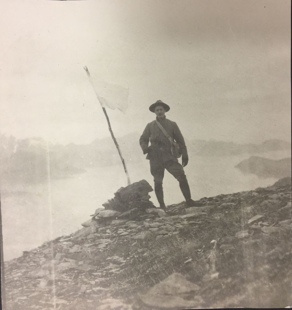 George E. Winter, the auditor for the Alaska Central Railway, standsat Race Point beside a cairn with a flag for a photo taken sometime between 1905 and 1908 when the Winters lived in Seward. Itacknowledge the importance of Race Point long before the first official Mount Marathon Race in 1915. (George Winter collection, courtesy of the Resurrection Bay Historical Society)