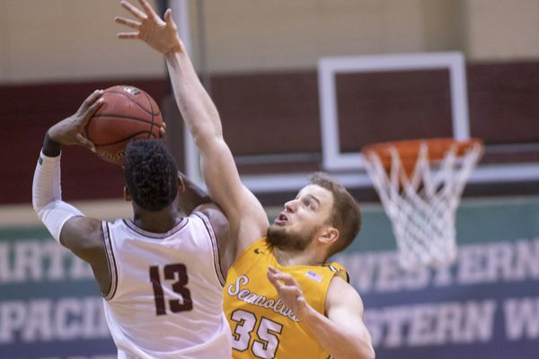 UAA juinor forward Oggie Pantovic attempts to block the shot of Seattle Pacific's Divant'e Moffitt during a GNAC tournament semifinal game Friday, March 6, in Seattle. (Photo by Matt Brashears)