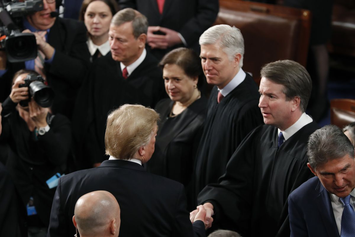 President Donald Trump shakes hands with Supreme Court Justice Brett Kavanaugh, after delivering his State of the Union address to a joint session of Congress on Capitol Hill in Washington, Tuesday, Feb. 5, 2019. Watching are from left, Supreme Court Chief Justice John Roberts, Associate Justice Elena Kagan and Associate Justice Neil Gorsuch. (AP Photo/J. Scott Applewhite)