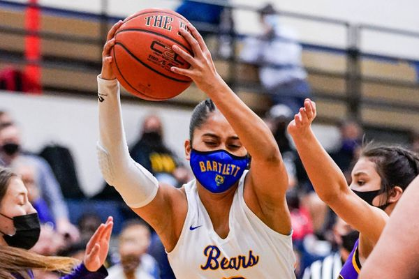Bartlett's Amelia Uhila jumps between Lathrop defenders during the 4A state championship basketball game against Lathrop on Saturday, March 27, 2021 in Palmer. Bartlett won 47-46 in overtime. (Loren Holmes / ADN)