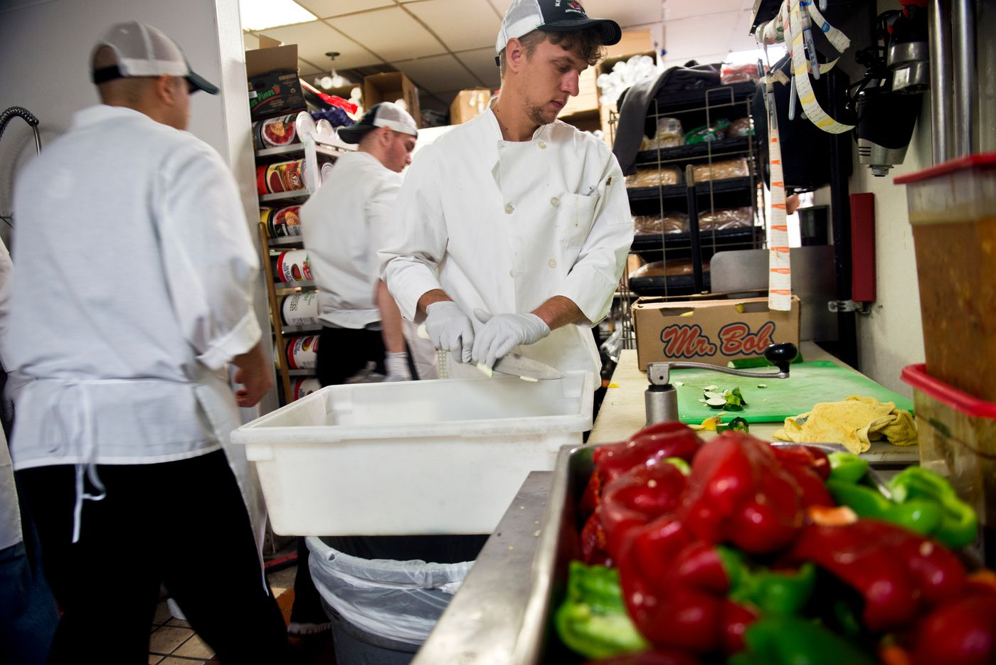 Milos Tatic, from Novi Sad, Serbia, cuts vegetables in the kitchen of Humpy's Alehouse. Tatic, in Anchorage on a J-1 visa program, said he also worked Pita Pit and gave private tennis lessons, a schedule that totaled 85-90 hours a week. (Marc Lester / Alaska Dispatch News)