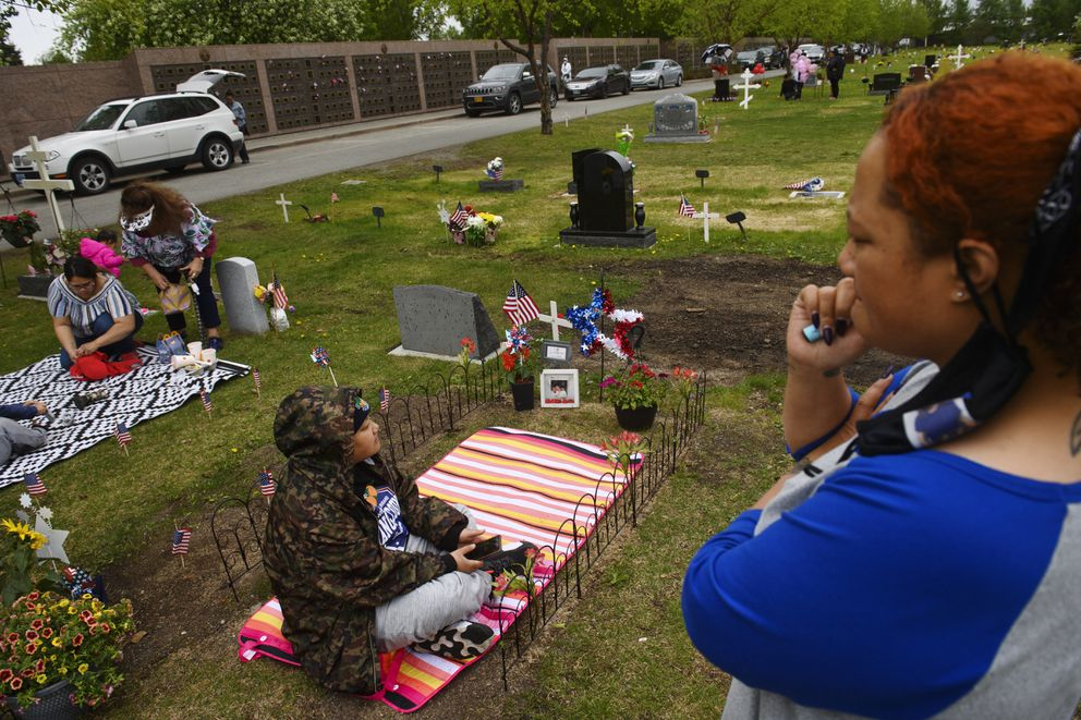 Tre Tavita, bottom, and Keekee Tauanuu visit the grave of their mother, Sierra Toia, at Anchorage Memorial Park Cemetery on May 31, 2021. (Marc Lester / ADN)