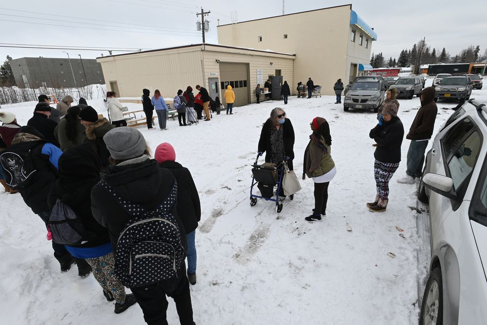 Angel Rickard, center, talks to her caregiver Juanita Bourgeois as they wait in line to receive a senior pantry box at the Lutheran Social Services of Alaska food pantry in Spenard on Wednesday, March 18, 2020. (Bill Roth / ADN)