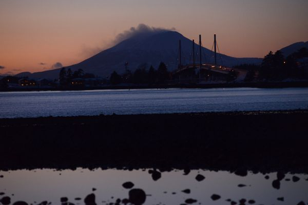 Vehicles travel across O'Connell Bridge that spans Sitka Channel between Japonski Island and Baranof Island. The sunset highlights a layer of clouds that hung on the top of Mt. Edgecumbe near Sitka, Jan. 10, 2020. (Anne Raup / ADN)