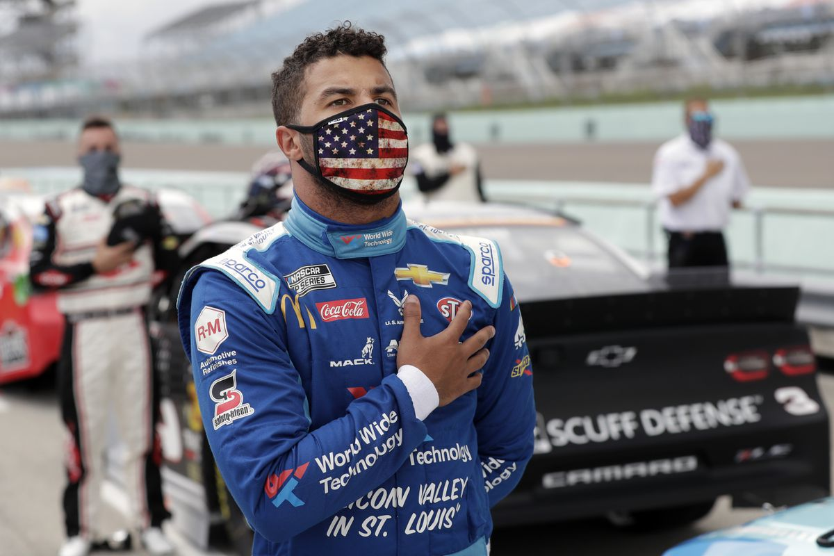 Bubba Wallace stands for the national anthem before a NASCAR Cup Series auto race Sunday, June 14, 2020, in Homestead, Fla. (AP Photo/Wilfredo Lee)