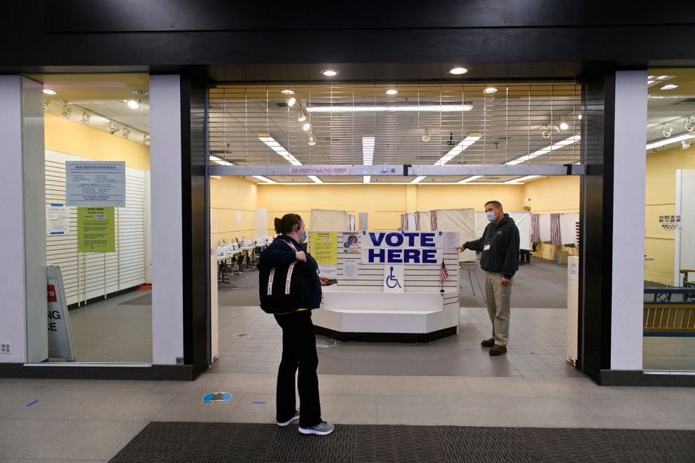 Bart Parker, right, shows a late voting arrival the hours of operation. (Marc Lester / ADN)