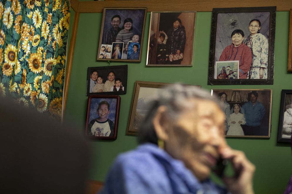Family pictures hang on the wall as Lizzie Chimiugak talks on the phone at her home in Toksook Bay, Alaska. (AP Photo/Gregory Bull)