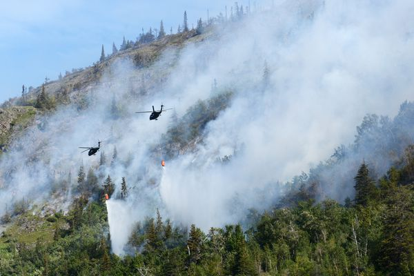 Alaska Army National Guard UH-60 Black Hawk helicopters drop water on the McHugh Creek wildfire as it continues to burn near Beluga Point on Wednesday, July 20, 2016, along Turnagain Arm. (Erik Hill / Alaska Dispatch News)