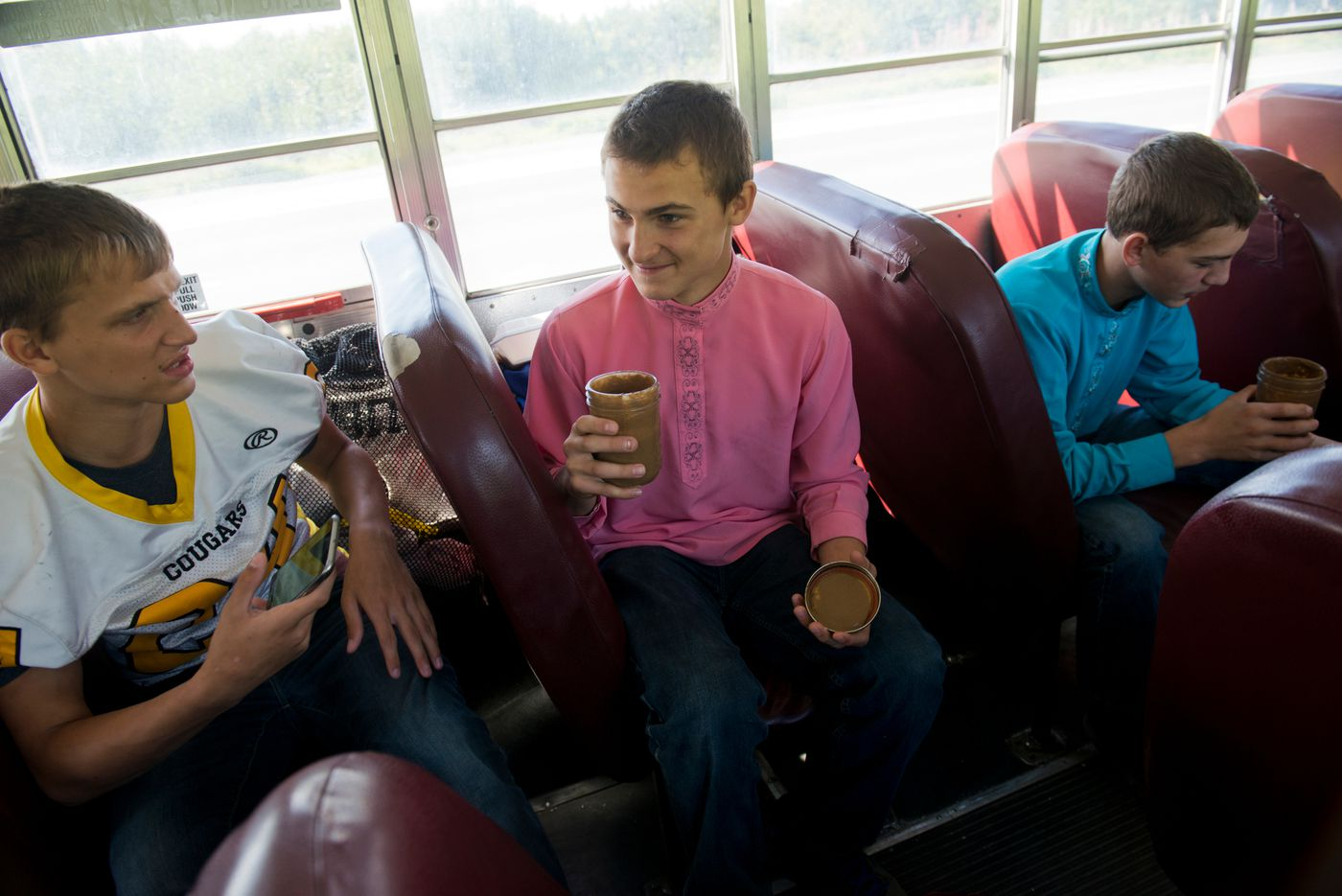 From left, Zasima Martushev, Kalinik Reutov and Jonah Reutov talk while they travel to an away football game on Friday, September 2, 2016. Coach Justin Zank said he's trying to teach the team about nutrition, and brought each player a smoothie to drink on the ride. (Marc Lester / Alaska Dispatch News)