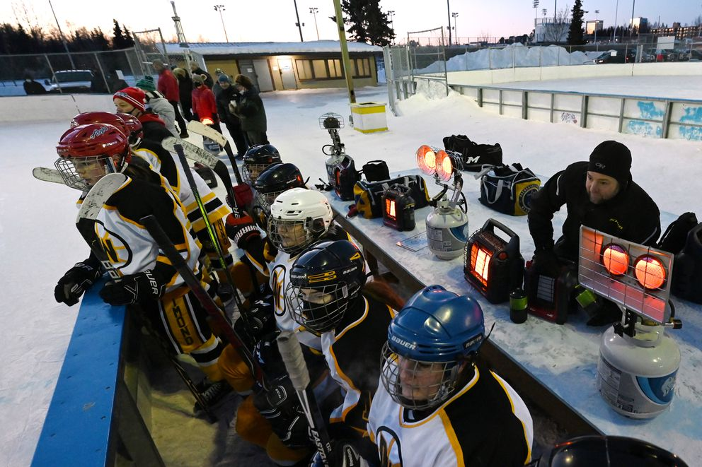 Rob Stone works on a propane heater behind the Dimond/West bench during a 2-0 loss to South/Bartlett in the first round of the girls high school hockey championships at the Bonnie Cusack Outdoor Ice Rinks on Monday, Feb. 1, 2021. (Bill Roth / ADN)