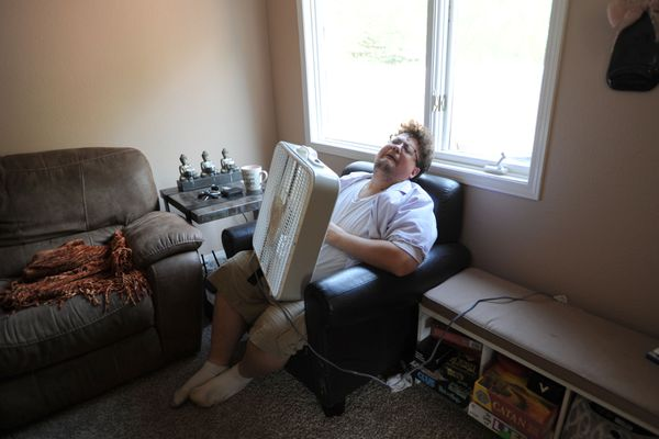 Seth Whipple has found a creative way to beat the heat on Friday, July 5, 2019. He's found that the fan has to be held out away from his body to achieve maximum cooling. (Anne Raup / ADN)