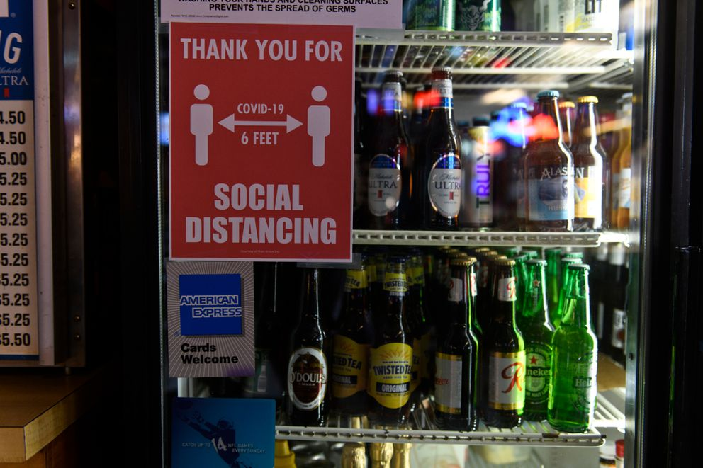 A social distancing sign is posted on a Crossroads Lounge refrigerator on May 7, 2020. (Marc Lester / ADN)