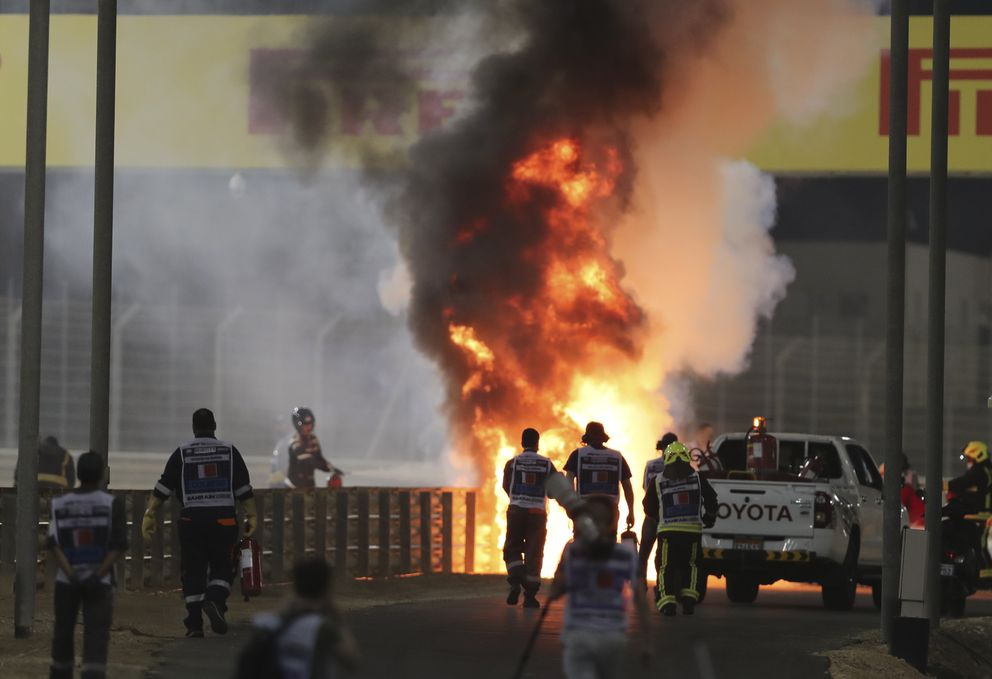 Marshals run to extinguish Haas driver Romain Grosjean's car after an accident during the Formula One Bahrain Grand Prix in Sakhir, Bahrain, Sunday, Nov. 29, 2020. cart the Formula One Bahrain Grand Prix in Sakhir, Bahrain, Sunday, Nov. 29, 2020. (AP Photo/Kamran Jebreili, Pool)