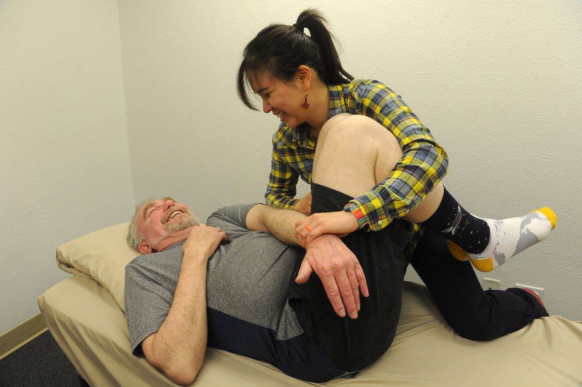 Bibo Chung of Peak Rehab LLC works with client Gary Levin in South Anchorage. (Bob Hallinen / ADN)