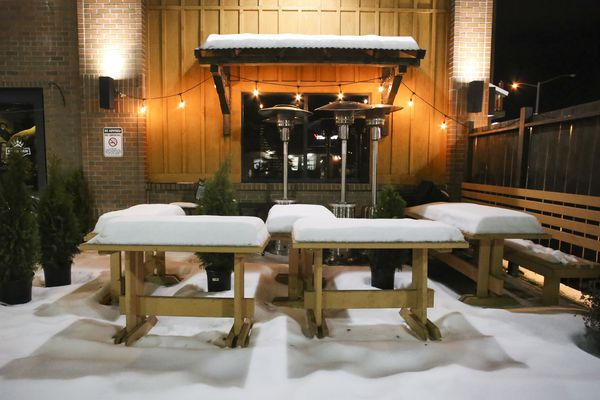 Outdoor tables and benches covered in snow rest in a corner at The Bear Paw Bar and Grill in Anchorage on Tuesday, Dec. 1, 2020. Anchorage returned to a modified