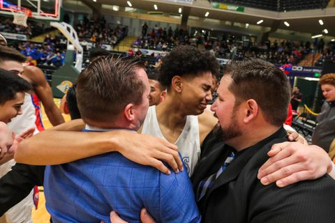 Anchorage Christian senior Demarcus Hall hugs his coaches Zack Madren, left, and Chet Dyson after making a game-winning free throw during the ASAA 3A State Basketball Championship against Valdez on Saturday, March 23, 2019 at the Alaska Airlines Center. Anchorage Christian won 56-53. (Loren Holmes / ADN)