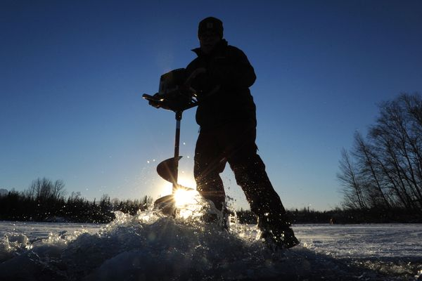 Marcus Adams, 18, used a power auger to drills holes into the frozen surface of Finger Lake will ice fishing on Sunday, Dec. 4, 2016. (Bill Roth / Alaska Dispatch News)