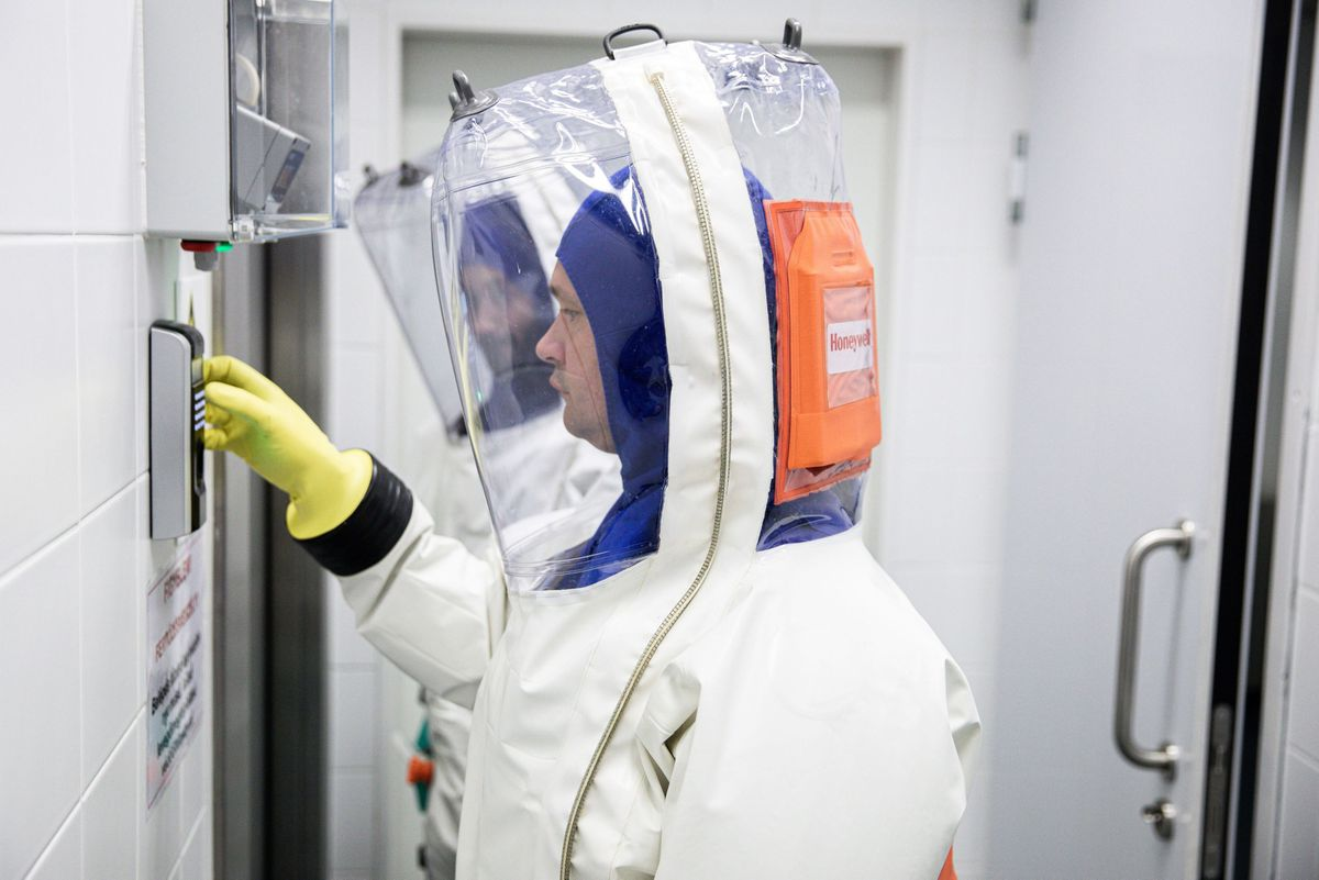 Scientists dressed in a full body protective suits enter a laboratory used for coronavirus research in Pecs, Hungary. MUST CREDIT: Bloomberg photo by Akos Stiller